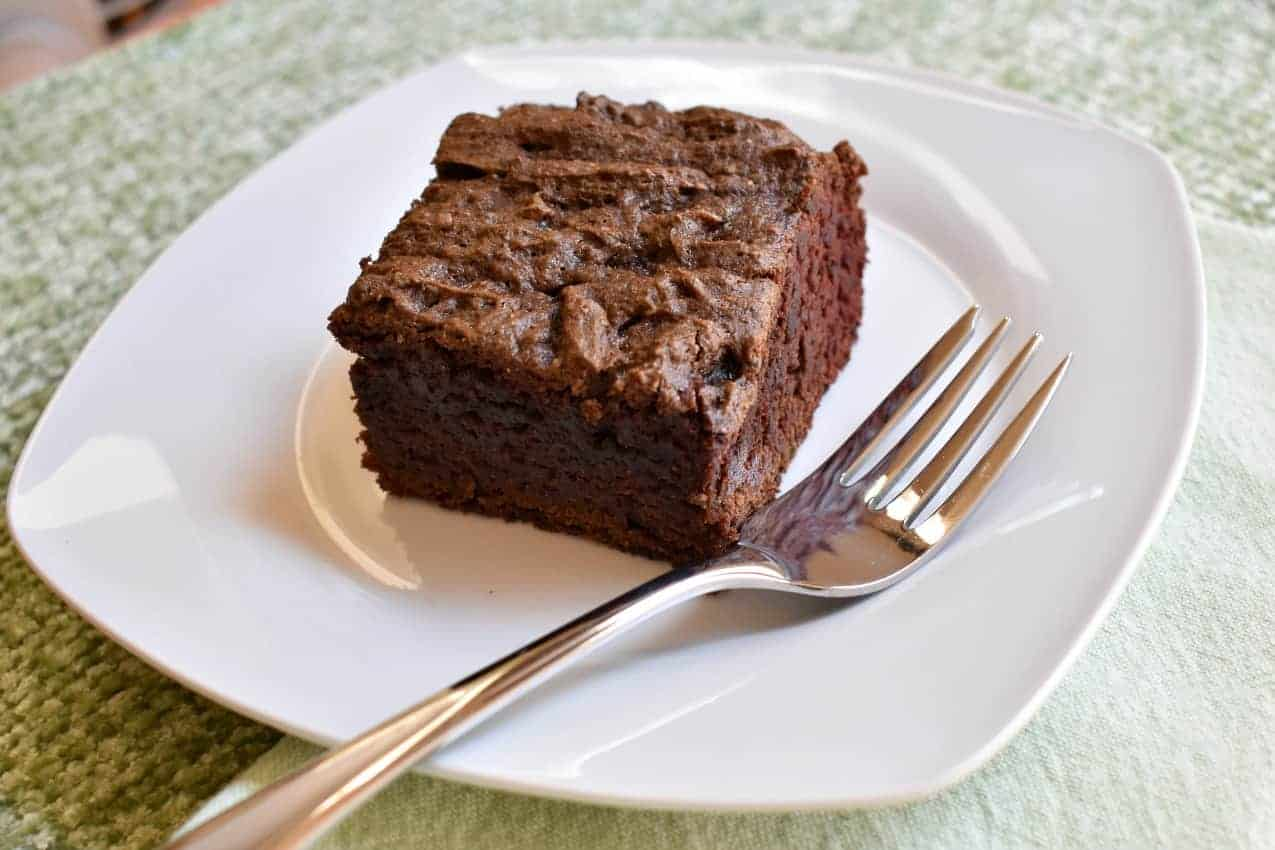 A slice of gluten free chocolate cake pan cake and fork on white plate on green placemat.