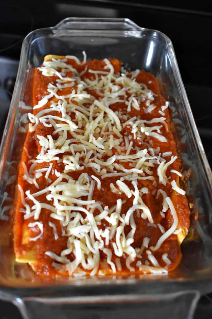 Close up view of unbaked Chicken Enchiladas for Two in glass loaf pan.