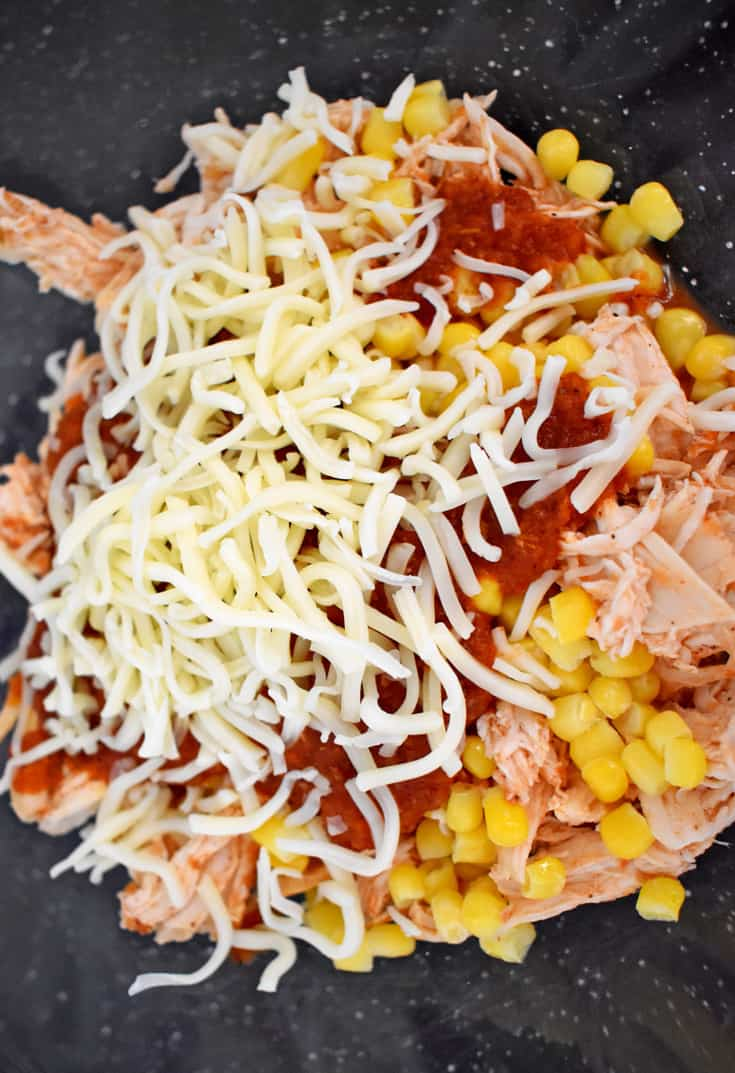 Overhead view of shredded chicken, corn, enchilada sauce, and shredded white cheese in glass mixing bowl.