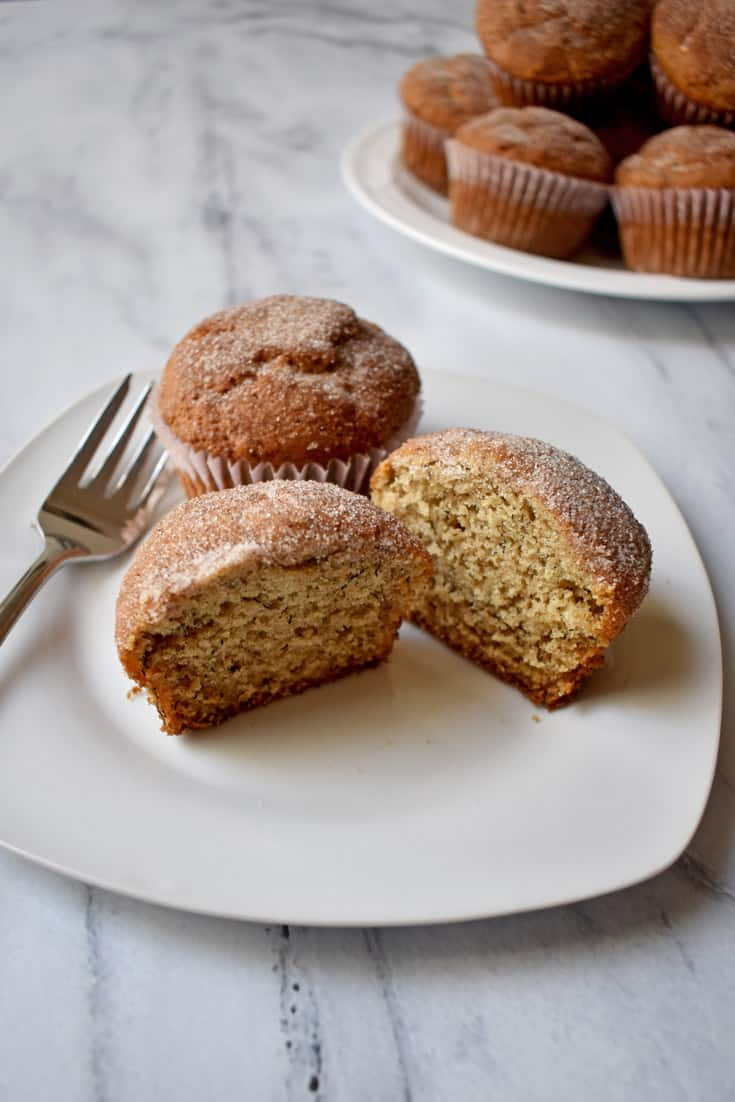 Two Gluten Free Cinnamon Banana Muffins on white plate with stack of muffins on white plate in background | Flavor Walk