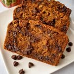 Slices of Gluten Free Chocolate Chip Pumpkin Bread on a white plate with chocolate chips | Flavor Walk