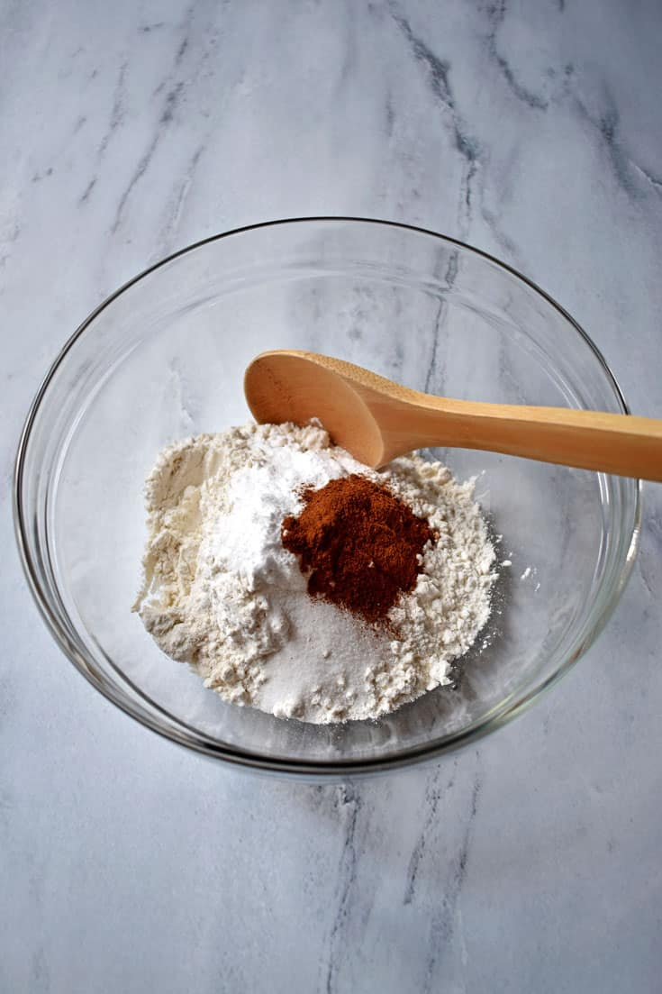 Gluten free flour, spices, and wooden spoon in small mixing bowl on granite countertop