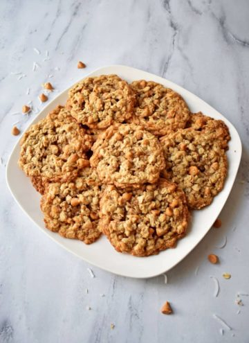 Stack of Toasted Coconut Butterscotch Oatmeal Cookies on white plate