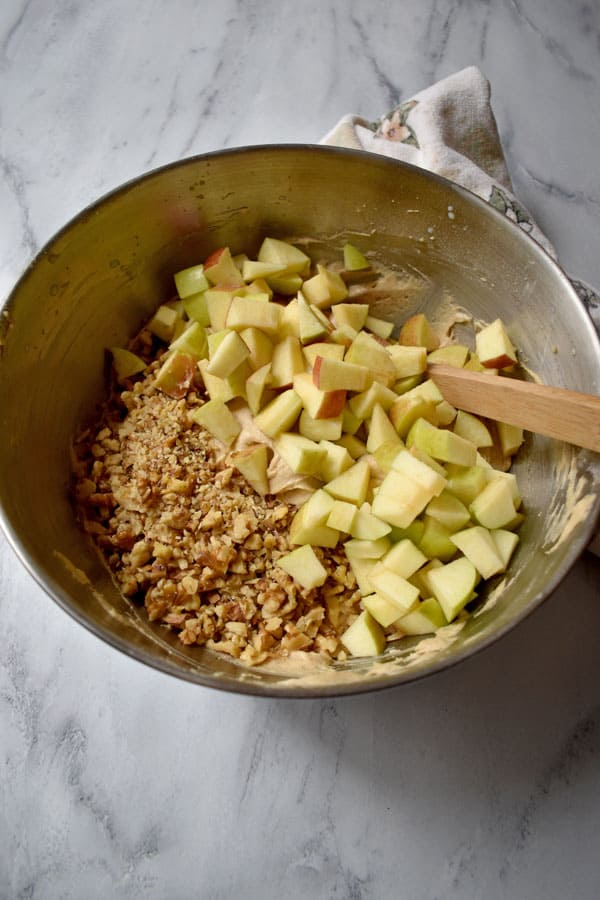 Apple Walnut Crumb Cake ingredients in large mixing bowl with apple pieces and chopped walnuts on top | Flavor Walk