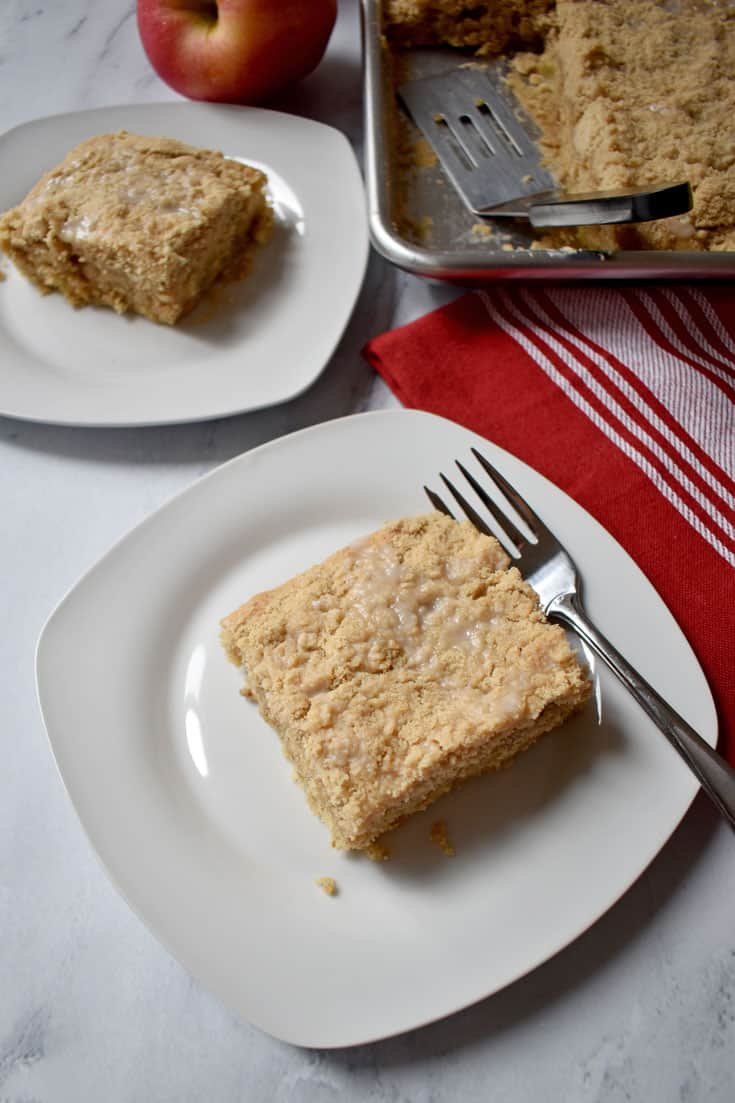Piece of Apple Walnut Crumb Cake {Gluten Free} on white plate, red dish cloth on the right, with sheet pan of cake in upper right corner and piece of cake on white plate in upper left corner | Flavor Walk