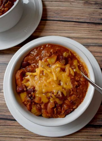 Chili with Beef, Turkey and Potatoes topped with melted cheddar cheese in white bowl on round white plate with silver spoon in bowl | Flavor Walk