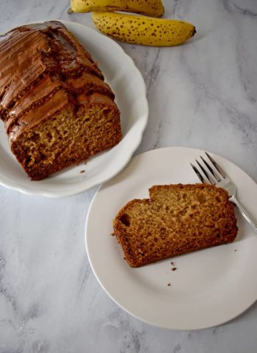 Sliced loaf of Caramelized Banana Bread {Gluten Free} on white plate in upper left corner and one slice of Caramelized Banana Bread {Gluten Free} on white plate in lower right corner. | Flavor Walk