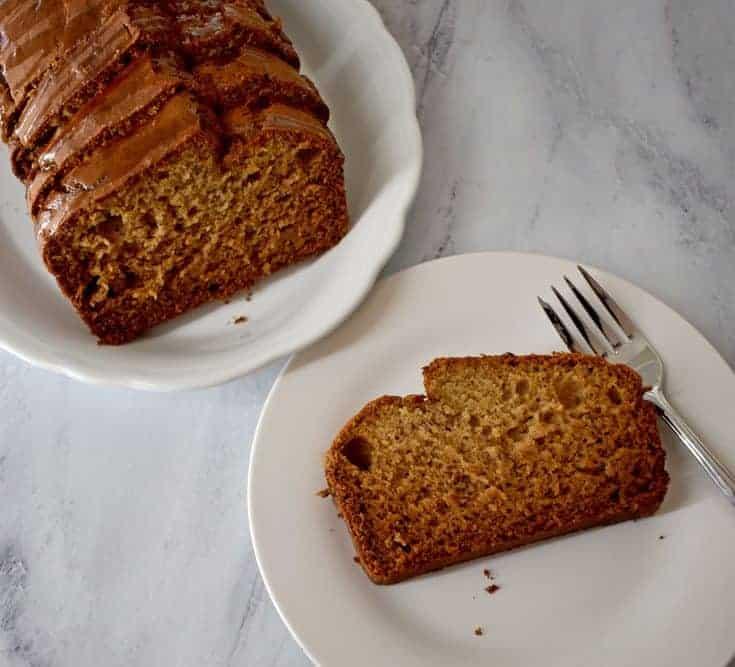 Sliced loaf of Caramelized Banana Bread {Gluten Free} on white plate in upper left corner and one slice of Caramelized Banana Bread {Gluten Free} on white plate in lower right corner. | Flavor Walk