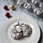 Three Gluten Free Chocolate Crinkle Cookies on white plate with additional cookies on wire rack in upper right corner | Flavor Walk