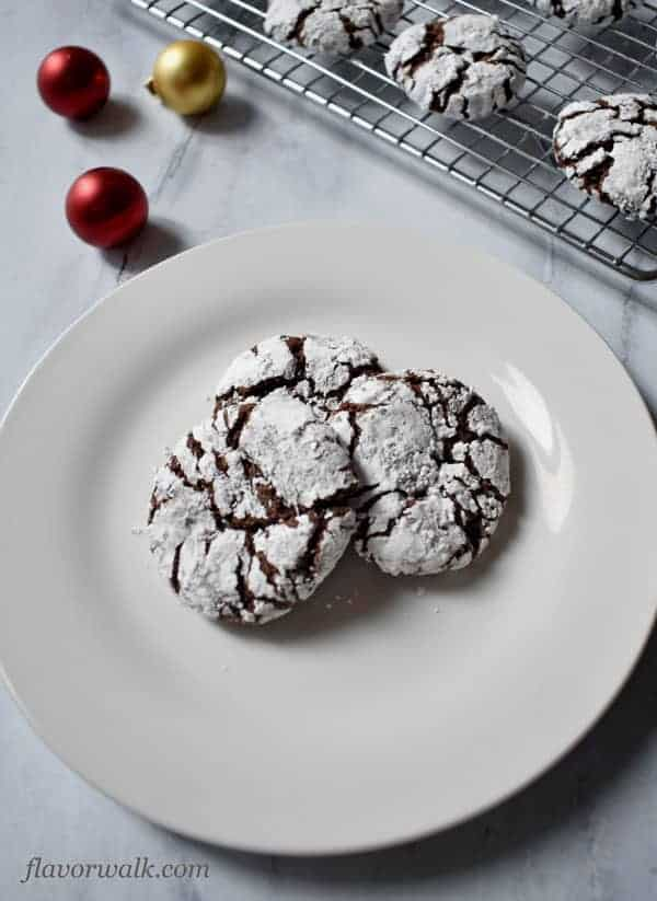 Close-up of 3 Gluten Free Chocolate Crinkle Cookies on white plate with additional cookies on wire rack in upper right corner | Flavor Walk
