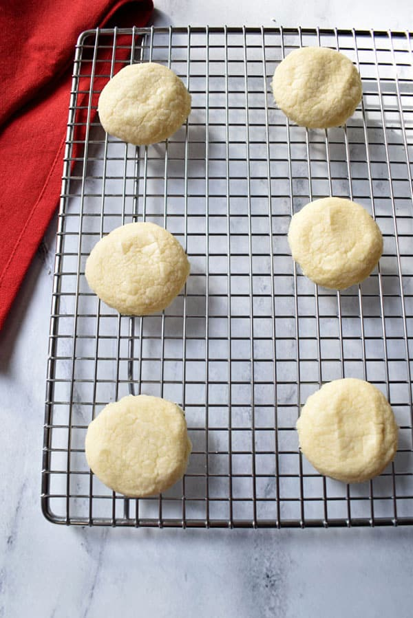 Unfrosted Gluten Free Peppermint Meltaway Cookies cooling on a wire rack with red kitchen towel in upper left hand corner | Flavor Walk