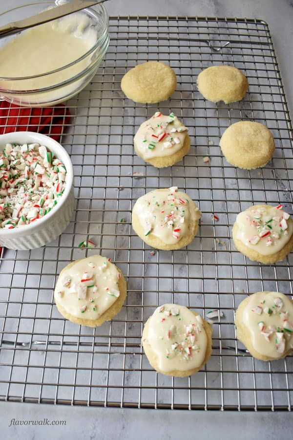 Gluten Free Peppermint Meltaway Cookies on wire rack with bowl of frosting and bowl of crushed candy canes | Flavor Walk