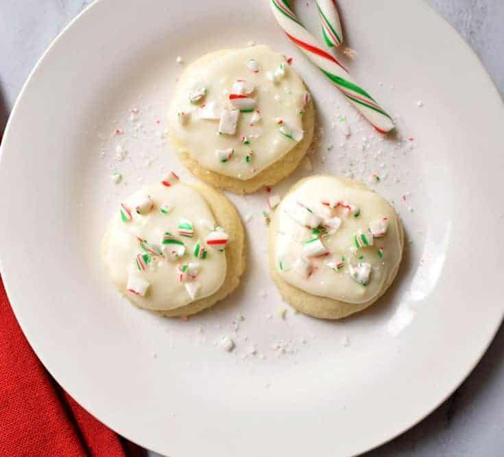 Three Gluten Free Peppermint Meltaway Cookies and a mini candy cane on white plate with red kitchen towel in the bottom left corner. | Flavor Walk