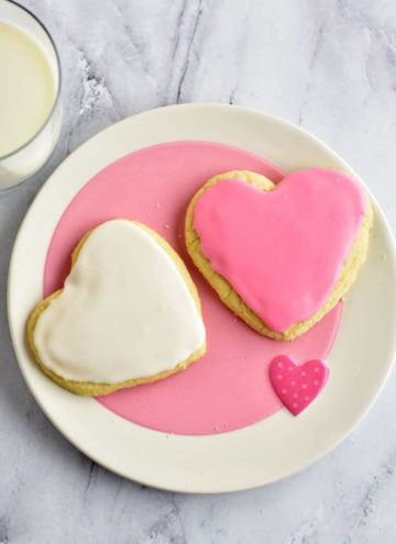 Two Frosted Powdered Sugar Cookies on a pink and white plate