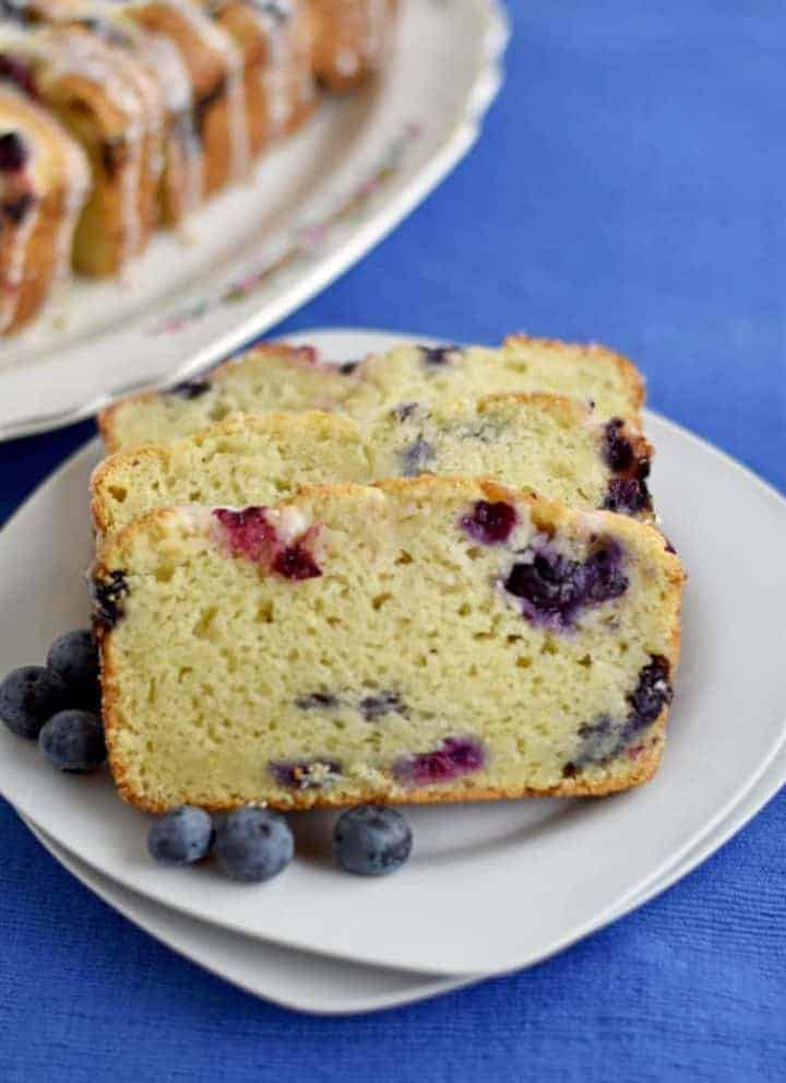 Three slices of Lemon Blueberry Bread with fresh blueberries on a white plate with more slices in the background