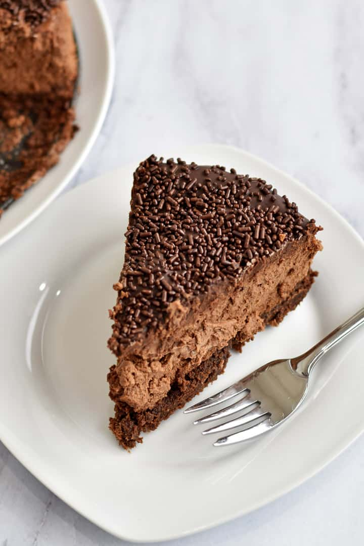Slice of Chocolate Brownie Cheesecake {Gluten Free} and fork on white plate
