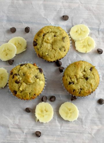 Three Gluten Free Chocolate Chip Banana Muffins on parchment paper with scattered banana slices and chocolate chips