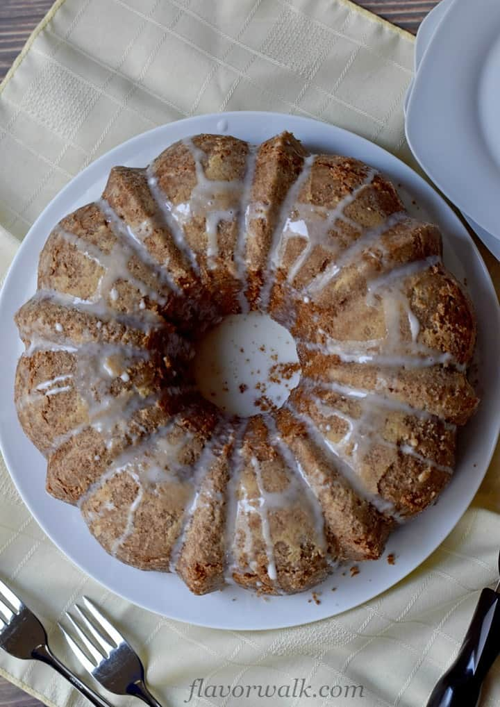 Overhead view of glazed sour cream coffee cake on white plate sitting on yellow napkin