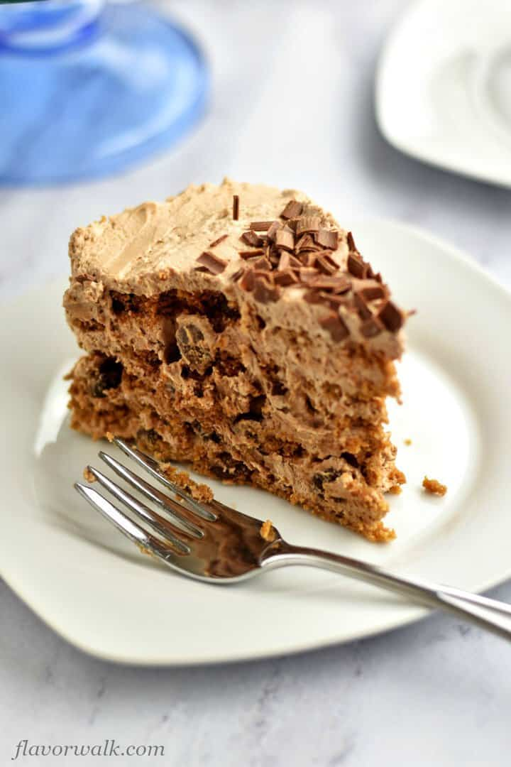 Close-up of slice of chocolate icebox cake with fork on white plate,