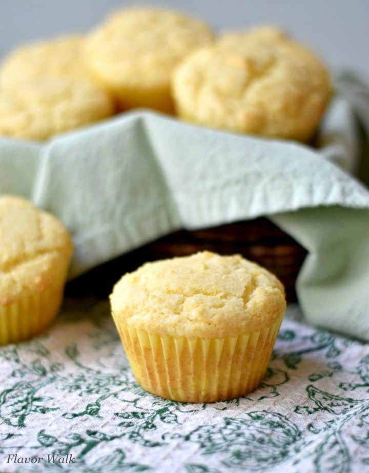 2 sweet cornbread muffins on a grean and white kitchen towel with a basket of muffins in the background