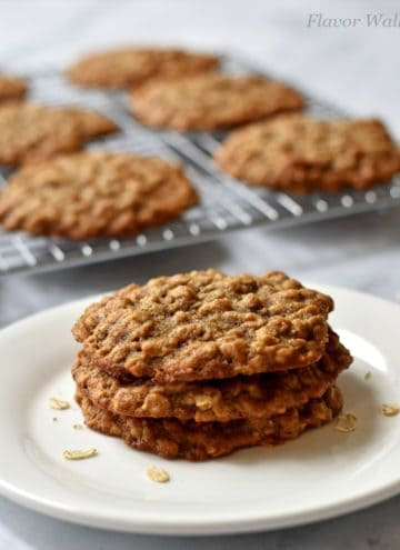 Stack of 3 banana oatmeal cookies on a white plate with additional cookies on a wire rack in the background