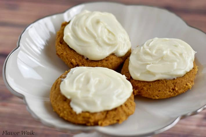 3 cream cheese frosted gluten free pumpkin cookies on silver-rimmed white plate