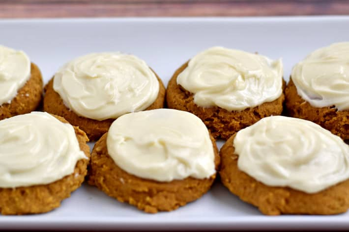 Gluten free pumpkin cookies with cream cheese frosting on white plate