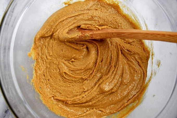 Overhead view of clear mixing bowl with peanut butter, brown sugar, bakding soda, and salt stirred together with wooden spoon
