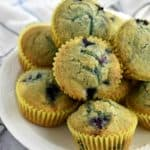 Stack of easy gluten free blueberry muffins on white plate with white striped kitchen towel in background