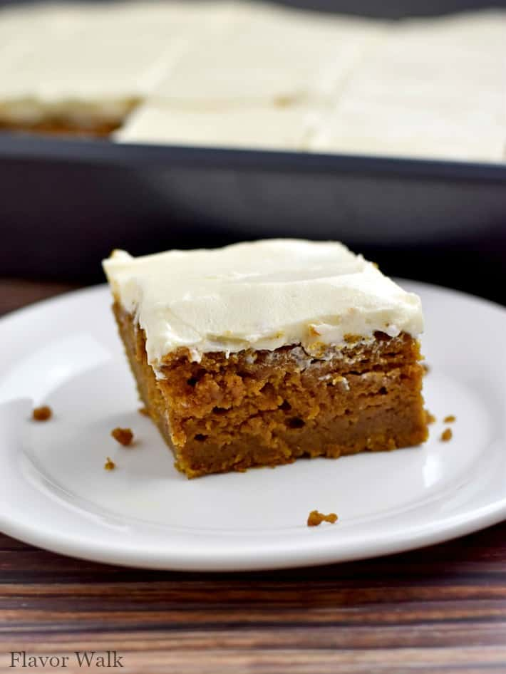 One gluten free pumpkin bar on white plate with pan of additional bars in background.
