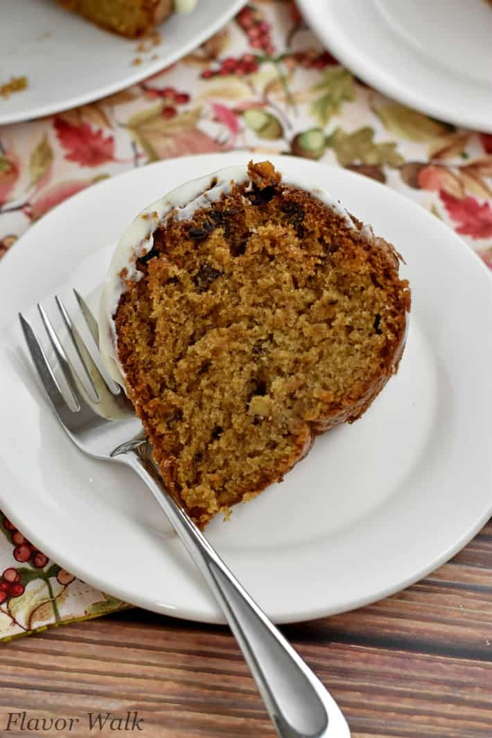 Overhead view of a slice of gluten free spice cake and fork on white plate