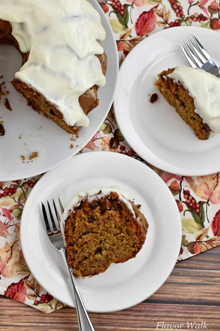 Slice of gluten free spice cake and fork on white plate with another slice in upper right corner and remaining cake in upper left corner