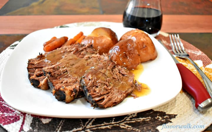 A serving of slow cooder beef pot roast and vegetables on white dinner plate with silverware to the right and a glass of red wine in the upper right corner