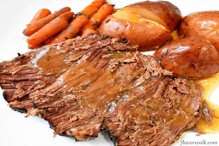 Slices of beef pot roast, red potatoes, carrots and gravy on a white plate