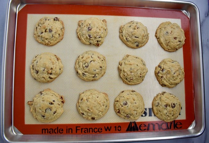Overhead view of silicone lined baking pan with baked chocolate chip peanut butter cookies