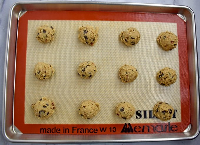 Overhead view of silicone lined baking pan with chocolate chip peanut butter cookie dough balls