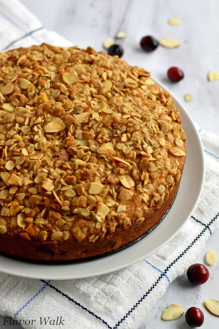 Whole cranberry coffee cake on white plate with cranberries and sliced almonds around the plate
