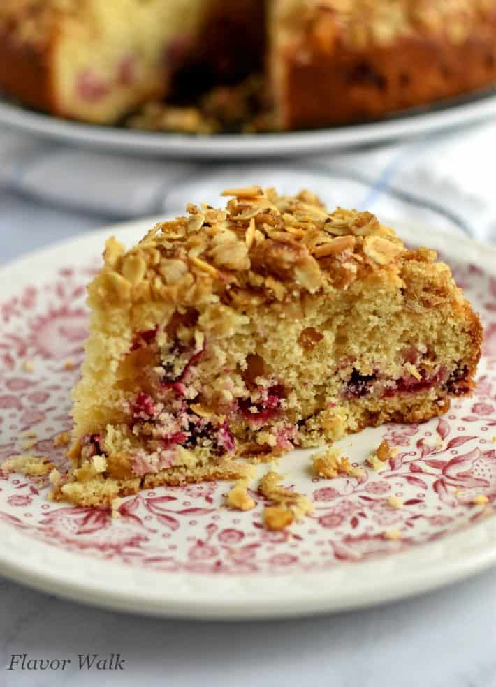 Slice of cranberry coffee cake on small white plate with red floral pattern and additional cake in the background