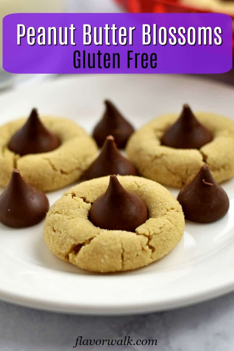Small white plate with 3 gluten free peanut butter blossoms surrounded by candy kisses with purple text overlay near top.