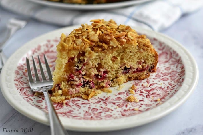 Close up picture of a slice of cranberry coffee cake and fork on small white plate with red floral pattern