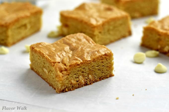 Gluten free blondies and white chocolate chips scattered on a piece of parchment paper