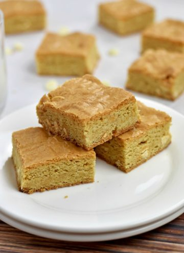 3 Gluten Free Blondies on a stack of 2 round white plates with a glass of milk and more blondies in background