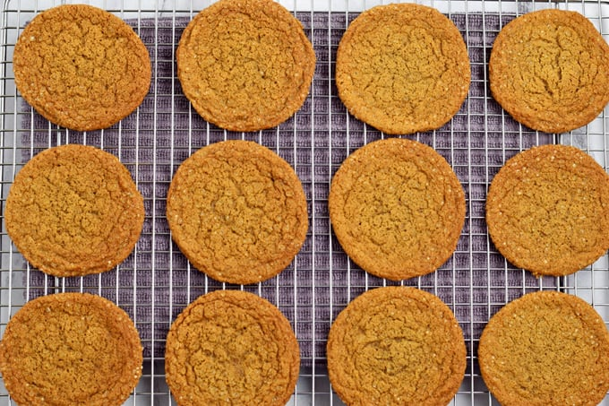 Overhead view of gluten free ginger snaps cooling on a wire rack with purple kitchen towel under the rack