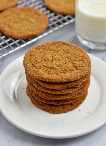 Stack of gluten free ginger snaps on small white plate with glass of milk and more cookies on wire rack in the background