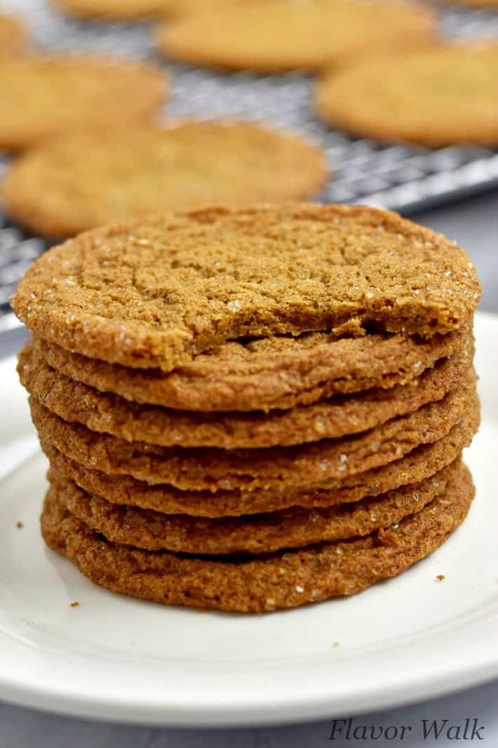 Stack of gluten free ginger snaps on small white plate and top cookie missing a bite with glass of milk and more cookies on wire rack in the background