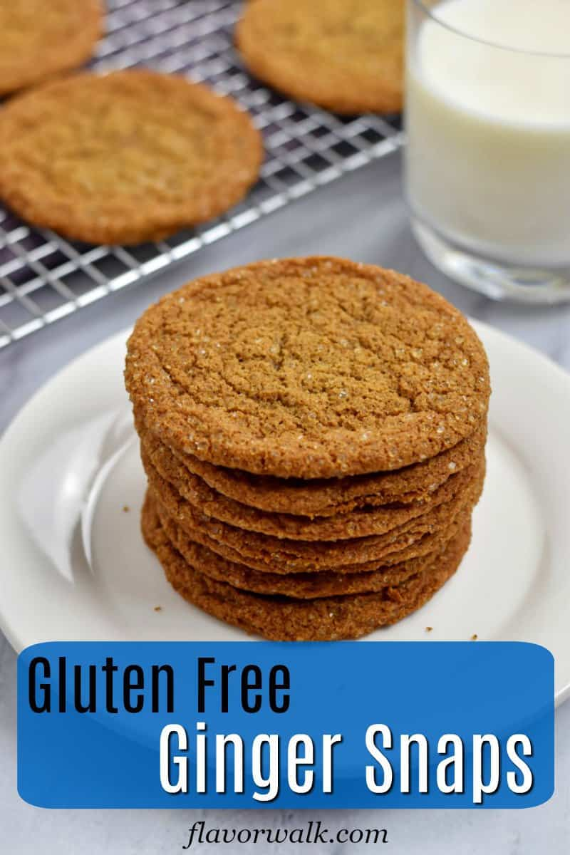 Stack of gluten free ginger snaps on small white plate with glass of milk and more cookies on wire rack in the background with blue text overlay near the bottom