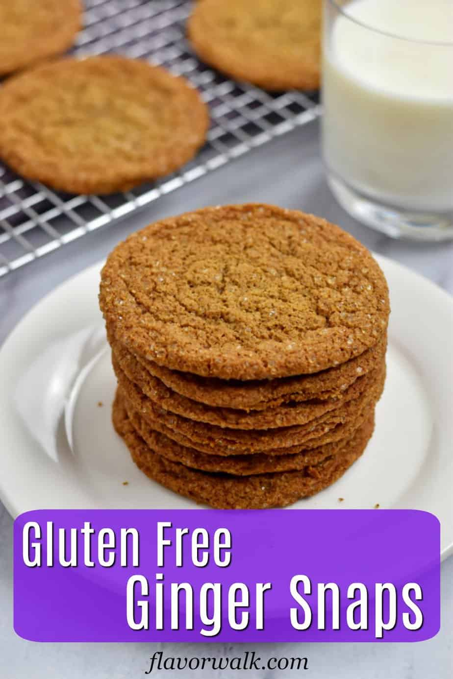 Stack of gluten free ginger snaps on small white plate with glass of milk and more cookies on wire rack in the background with purple text overlay near the bottom