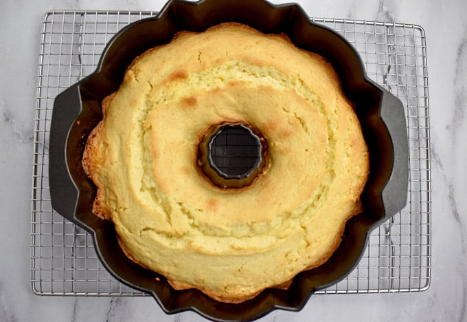 Overhead view of baked gluten free lemon cake in bundt pan on wire rack.