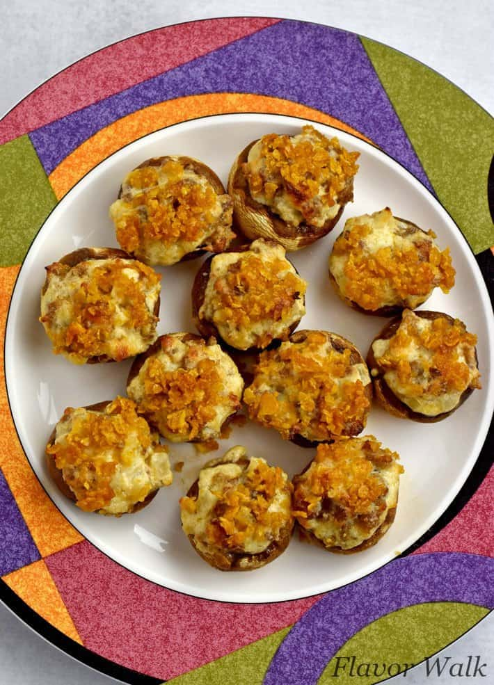 Overhead view of white plate with colorful edge filled with gluten free stuffed mushrooms.