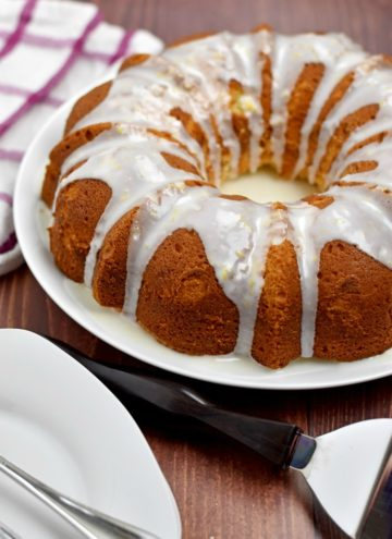 Gluten Free Lemon Cake on round white plate with small white plates and cake server in front